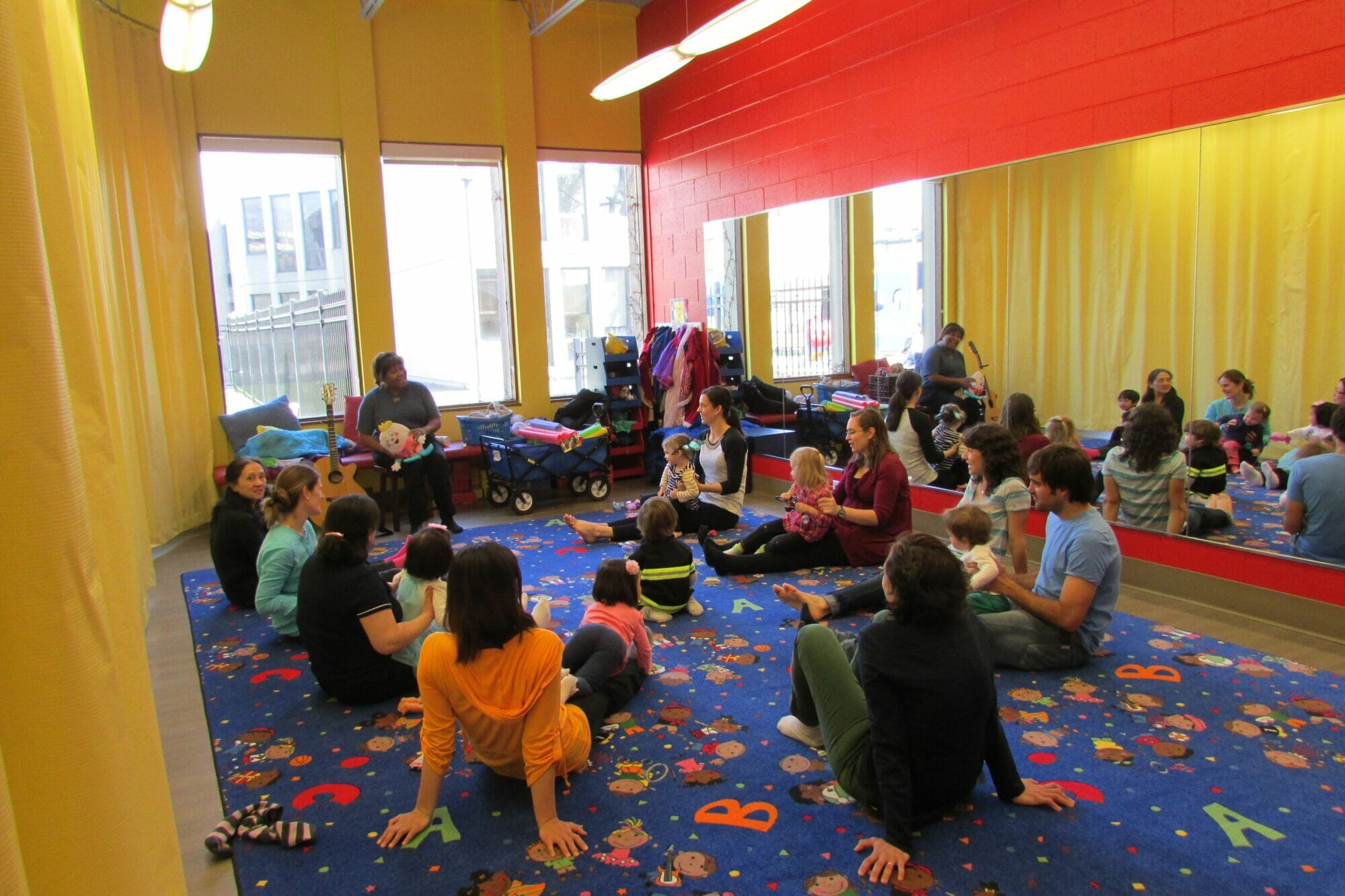 People sit in a circle with their children for an activity.