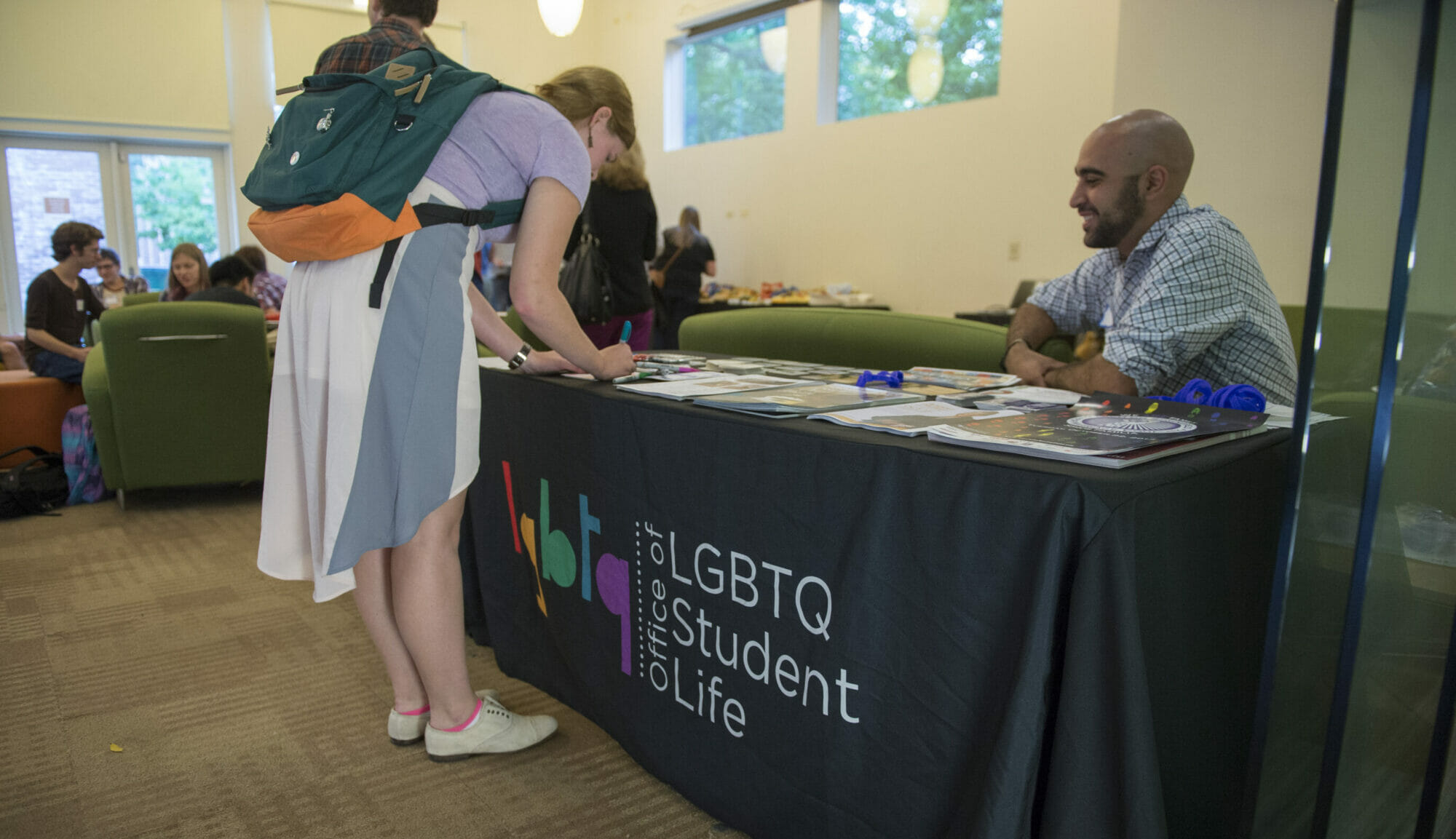 A student wearing a backpack writes a nametag at a check-in table with the LGBTQ Student Life logo